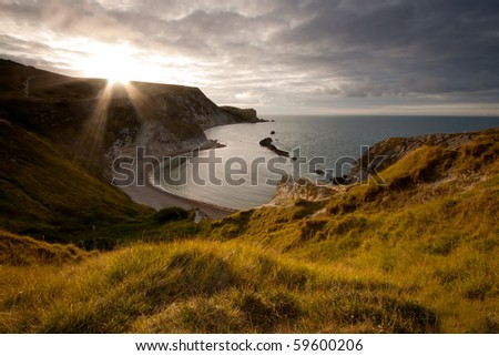 The sun peeps out over the cliff top over looking Man-O-War Cove on the Jurassic Coast in Dorset, UK. - stock photo