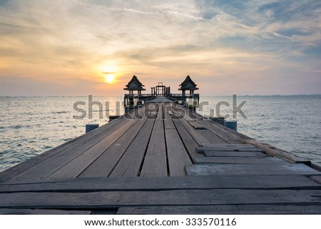 The sun reflected off the wooden bridge that stretches into the sea.In Chonburi Thailand. - stock photo