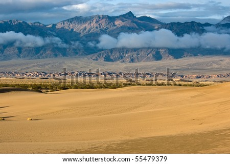 The sun rises on Mesquite Flat Sand Dunes under layers of sunlit mountains and clouds in Death Valley National Park, California. - stock photo