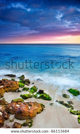 The sun rises over a gorgeous beach with mossy rocks - stock photo