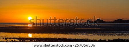 The sun rises over a wide expanse of mudflats in Swansea Bay, with the Mumbles skyline on the right. - stock photo