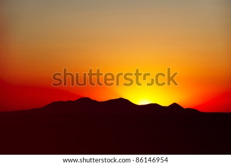 The sun rises over mountain range and paints a dramatic sky somewhere out west. - stock photo
