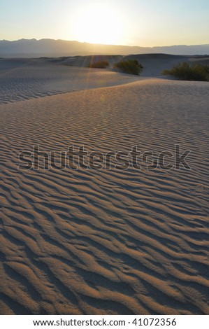 The sun rises over the desert in Death Valley. - stock photo