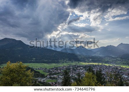 the sun's rays piercing through the clouds over the mountain village