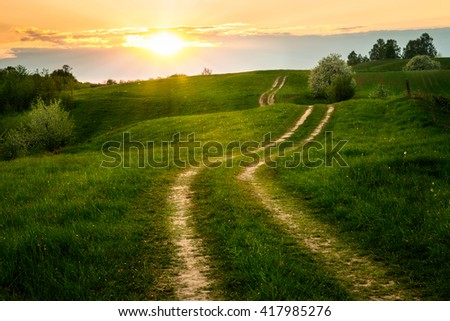 The Sun set over the dirt, winding road. May 2016, Masuria, Poland. - stock photo
