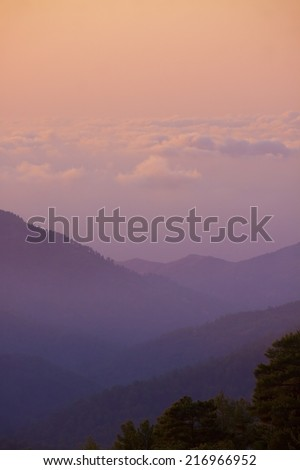 The sun sets above clouds at altitude in the Troodos Mountains - stock photo