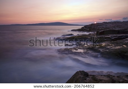 The sun sets against a rocky coast at Schoodic Point in Acadia National Park, Maine. Long exposure to achieve the misty effect of the ocean. - stock photo