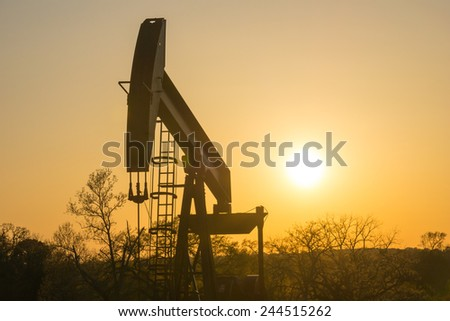 The Sun sets behind a Texas oil well. - stock photo