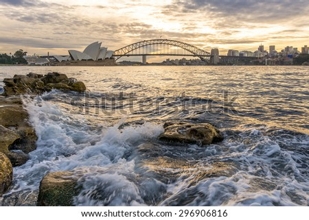 The sun sets behind the Harbour Bridge and Opera House in Sydney. - stock photo
