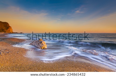 The sun sets illuminating the wet rocks and pebble beaches of the Jurassic Coast - stock photo
