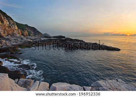 The sun setting over the ocean and mountains. - stock photo