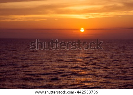 The sun setting over the ocean as seen from a cruise ship. - stock photo