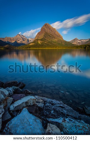 The sun shines at Mount Wilbur in the morning, Swift Current Lake, Glacier National Park - stock photo