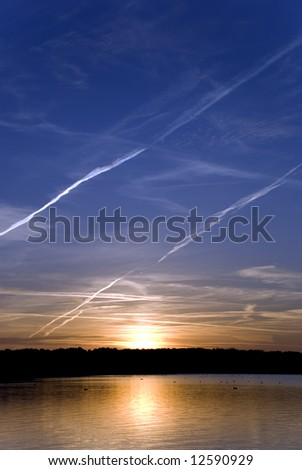 The sun shining on horizon behind cloud - stock photo