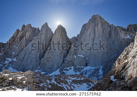 the sun slips behind Keeler Needle next to Mount Whitney and Day Needle or Crooks Peak in the high Sierra Nevada Mountains - stock photo