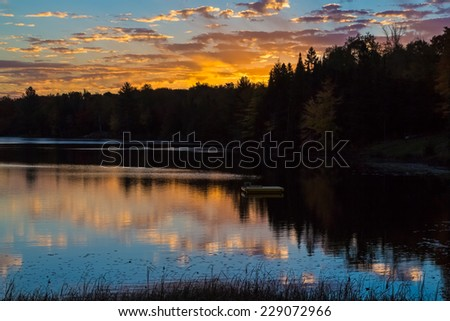 The sunrise sky illuminates that waters of a large pond in Michigan's Upper Peninsula. - stock photo