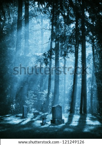 The suns rays breaks through the morning fog and highlight the headstones in a rural cemetery. - stock photo