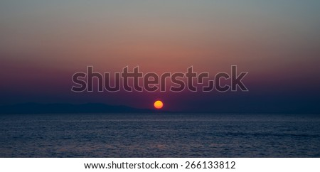 The sunset and the island of the Mediterranean - stock photo