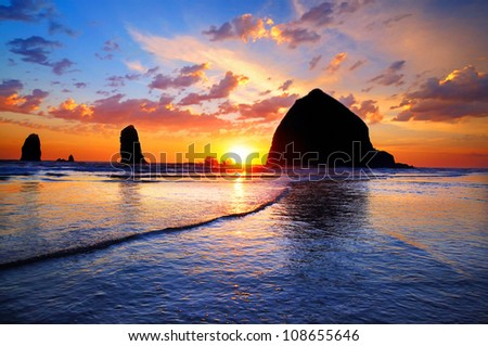 The Sunset at Cannon Beach with Dramatic clouds in the background and a nice reflection - stock photo