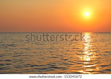 The sunset on the sea coast in Greece - stock photo
