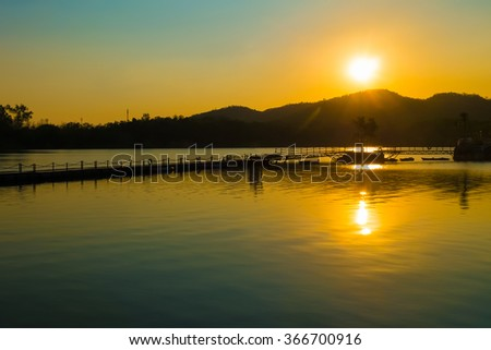 The sunset over the lake and the mountains in Thailand.