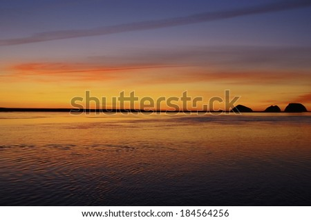 The sunset turns the sky golden as it silhouettes Three Arch Rocks on the Pacific Coast of Oregon in the northwest United States - stock photo