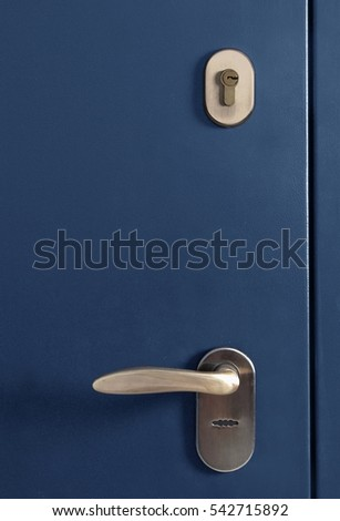 The surface of a metal door with lock and handle