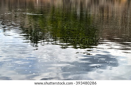 The surface of a pond with rippling gentle waves and reflections of trees and blue sky. - stock photo