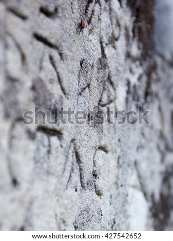 The surface of the old cross gravestone with engraved Old Church Slavonic inscriptions. Kyiv, Ukraine. Close up. - stock photo