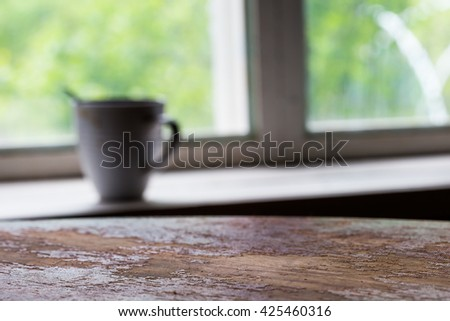 The surface of the old table with the silhouette of the Cup against the window.