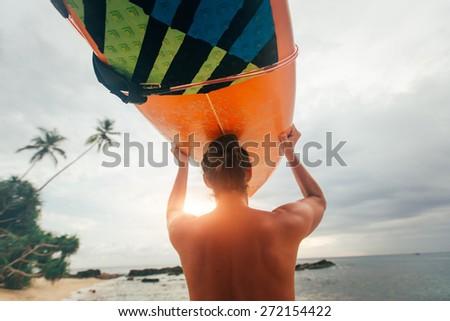 The surfer bears surfboard on the head - stock photo