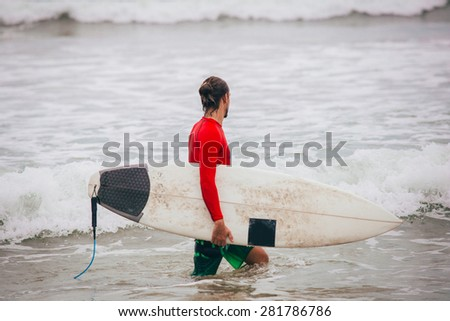 The surfer comes into the ocean - stock photo