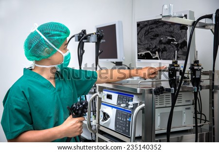 The surgeon looks at the monitor during surgical operation - stock photo