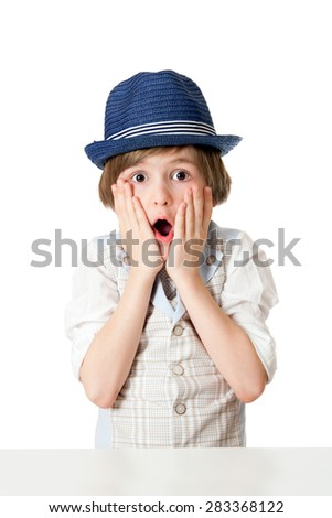 The surprised boy with expressive face in the blue hat - stock photo
