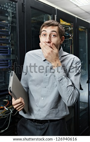 The surprised engineer stand in data center near telecommunication equipment with tablet PC.