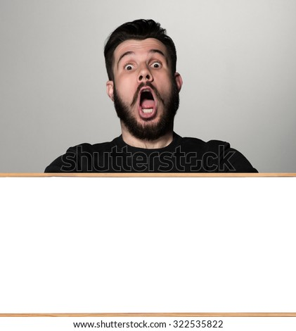 The surprised man and empty white blank or copyspace over gray background