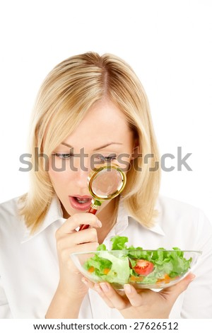 The surprised woman considers through a magnifier the vegetables, isolated - stock photo