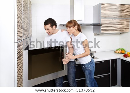 The surprised young couple looks in an oven on kitchen - stock photo