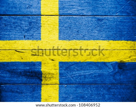 The Swedish flag painted on wooden surface - stock photo