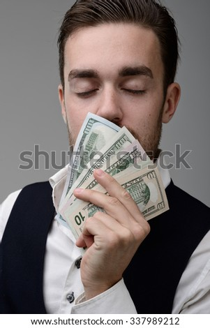 the sweet smell of money. a young man sniffing the money and dreams - stock photo