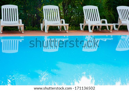 the swimming pool with some chairs - stock photo