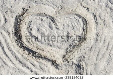 The symbol of heart is drawn on sand - stock photo
