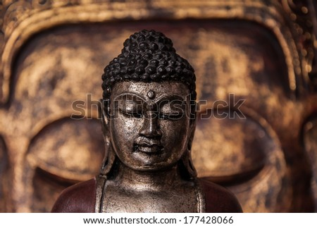 The symbol of the richness, of the founder of Buddhism, Buddha miniature statue sculpture with golden painted wood carved Buddha face on the background - stock photo