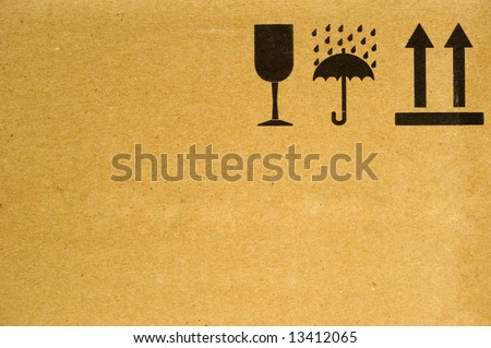 The symbols 'fragile', 'keep dry' and 'this way up' on the side of a cardboard box. Space for text on the cardboard.