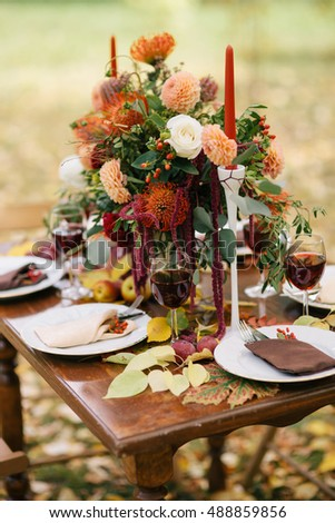 The table decorated with flowers and candles in an autumn garden.