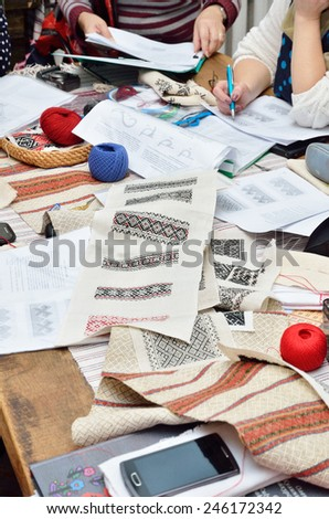 The table is covered with handmade samples, paper sheets, yarn and threads, pieces of cloth during the tuition of needlecraft.  - stock photo