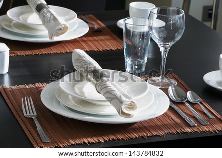 The table is set for a western style dinner. The white crockery contrasts wonderfully against the dark wooden table - stock photo