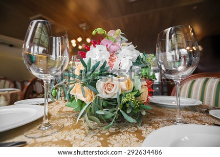 the table with flowers is served a holiday dinner in restaurant