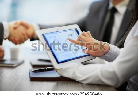 The tablet with the schedule in the foreground. Business partners shaking hands in office. - stock photo