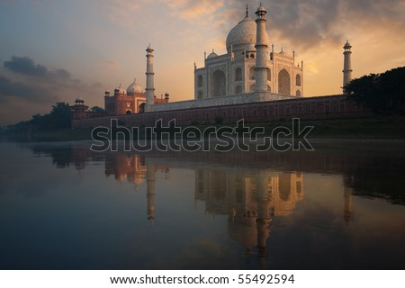 The Taj Mahal glows brilliantly from a colorful sunset seen from the holy Jamuna river. - stock photo